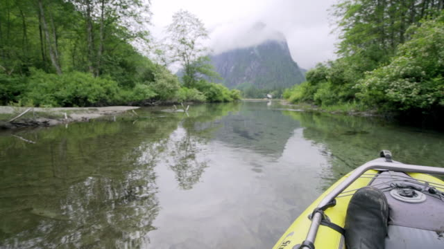 Bow of Kayak Drifting Down River in Vancouver, Canada with Man's Shoe Visible