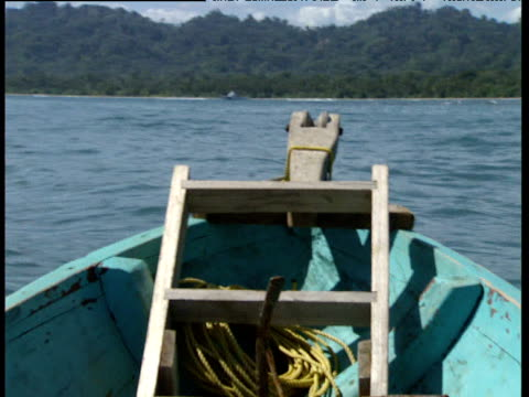 bow of small wooden fishing at sea slowly sails towards tree lined coast trinidad and tobago - anker werfen stock-videos und b-roll-filmmaterial