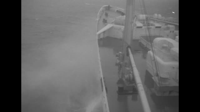 bow of the liner ss united states moving through the water / fireboats shooting water jet salutes with people waving from a railing of the ship they... - normandie stock-videos und b-roll-filmmaterial