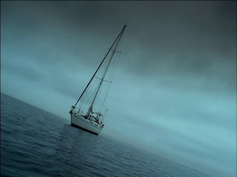 bow of yacht with sails lowered floats on calm sea, south africa - tauwerk stock-videos und b-roll-filmmaterial