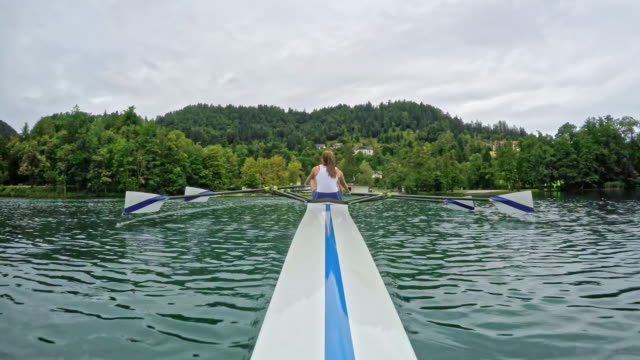 pov bow view of a female athlete sculling on a lake - sculling stock videos & royalty-free footage