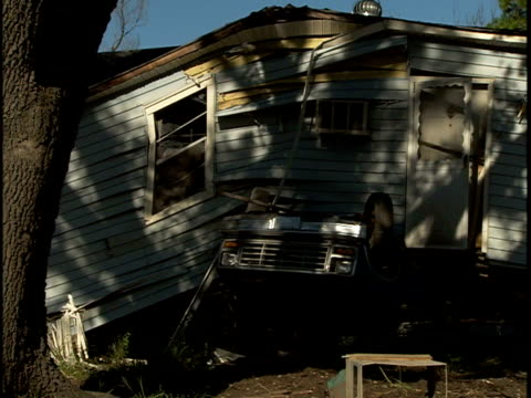 bowed house on top of upside-down car or truck, window & door framing at unnatural angle, screen door slightly ajar. totaled, low income area,... - ajar stock videos & royalty-free footage