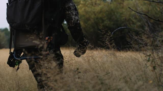 vidéos et rushes de un bowhunter marche lentement à travers les buissons, suivi de sa proie. la caméra titres de gros plan sur les pieds du chasseur à un large et il marche, porter son arc avec son gros sac sur son dos. - armement