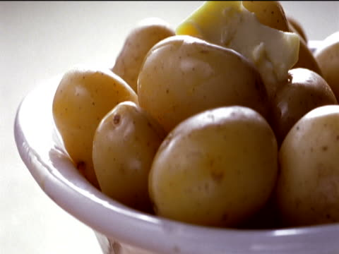 bowl full of potatoes covered with melting butter and a herb garnish - medium group of objects stock videos & royalty-free footage