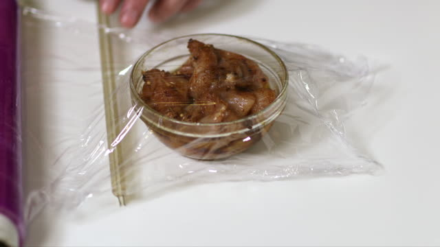 bowl marinated chicken chops in household film. - polyethylene stock videos and b-roll footage