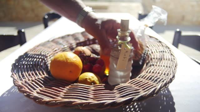 Bowl of fruit in sun with local gift, raki.