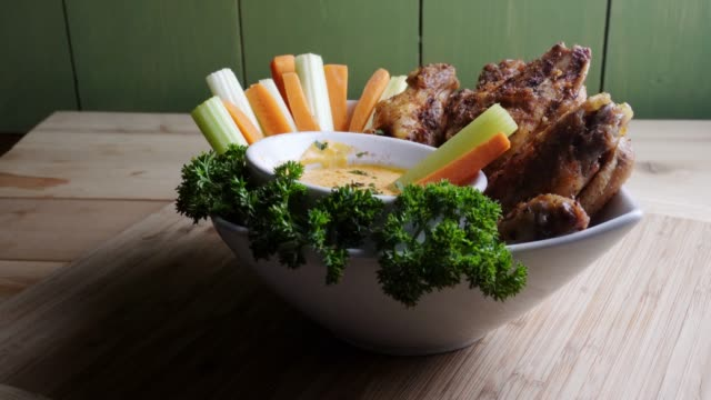 a bowl of healthy baked grilled chicken wings accompanied by hot sauce celery and carrot sticks - ranch dip stock videos & royalty-free footage