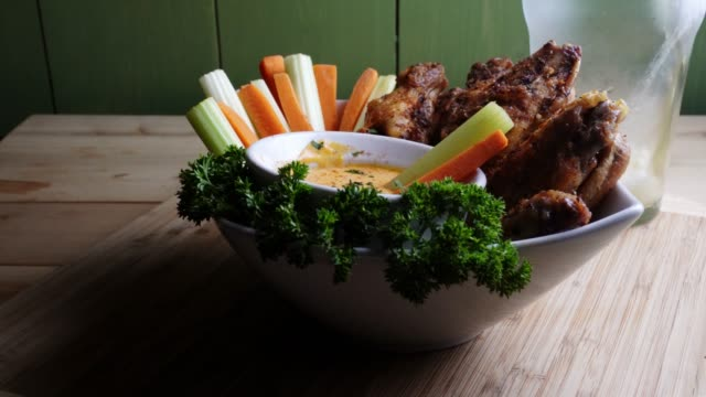 a bowl of healthy baked grilled chicken wings accompanied by hot sauce celery and carrot sticks with a beer - dipping stock videos & royalty-free footage
