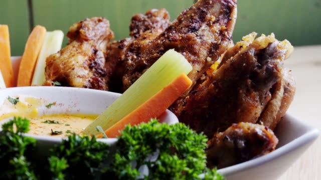 a bowl of healthy baked grilled chicken wings accompanied by hot sauce celery and carrot sticks - tray stock videos & royalty-free footage