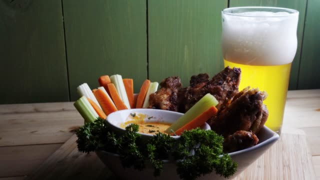 a bowl of healthy baked grilled chicken wings accompanied by hot sauce celery and carrot sticks with a beer - ranch dip stock videos & royalty-free footage