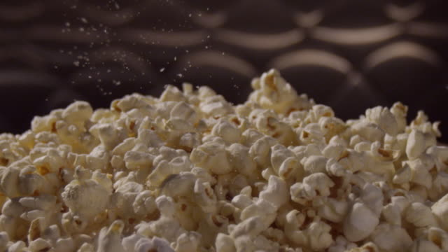 vídeos de stock, filmes e b-roll de a bowl of popcorn is seasoned with salt. - pipoca