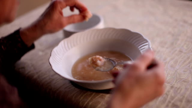 Bowl of soup and hand holding spoon