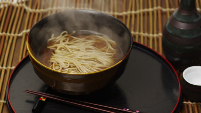 cu bowl of steaming hot soba (buckwheat noodles) and kitsune, slice of fried tofu and spring onion added later / tokyo, tokyo-to, japan - steam stock videos & royalty-free footage
