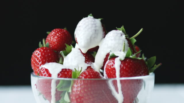vidéos et rushes de bowl of strawberries coated in cream with cream dripping off a singular strawberry - coupe à fruits