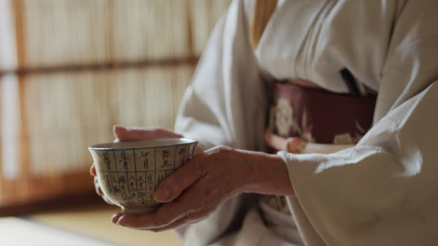 bowl of tea steaming in hands of japanese tea ceremony host - traditional ceremony stock videos & royalty-free footage