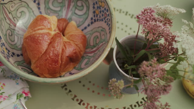 bowl with fresh croissants on table with flowers - croissant stock videos & royalty-free footage