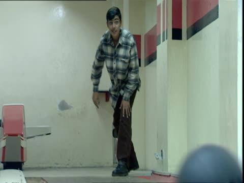 bowler in plaid shirt rolling ball down alley / baghdad, iraq - plaid shirt stock videos & royalty-free footage