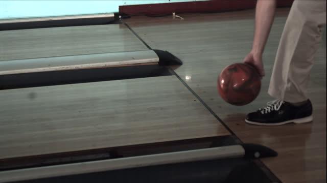 vídeos de stock, filmes e b-roll de a bowler releases a ball down a bowling lane. - sapato de boliche