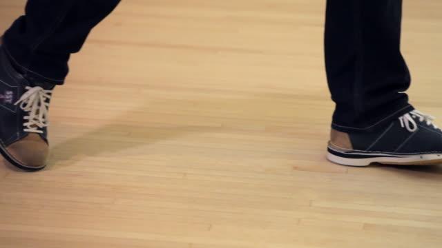 vídeos de stock, filmes e b-roll de bowler's feet as he throws a bowling ball and misses - sapato de boliche