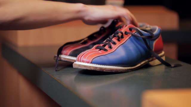 vídeos de stock, filmes e b-roll de bowler's hand gives back bowling shoes - sapato de boliche
