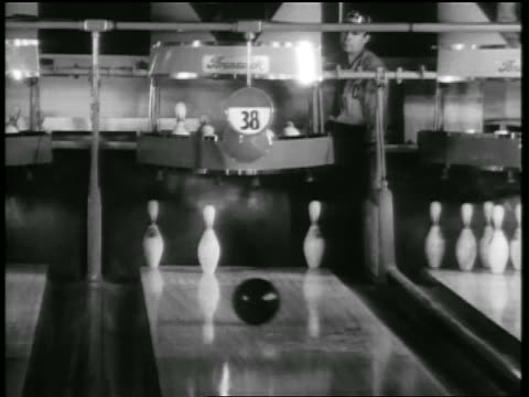 b/w 1938 bowling ball knocking three pins down for a spare (split) / pinsetter watching / chicago - bowling ball stock videos & royalty-free footage