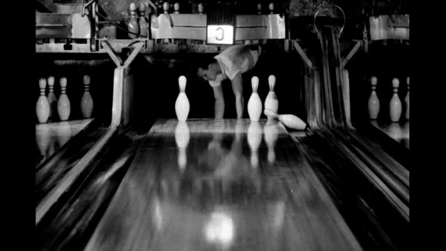 vídeos de stock, filmes e b-roll de bowling balls rolling down alley knocking down pins pinboy pulling pins from lane bowling alley on january 01 1940 - cancha de jogo de boliche