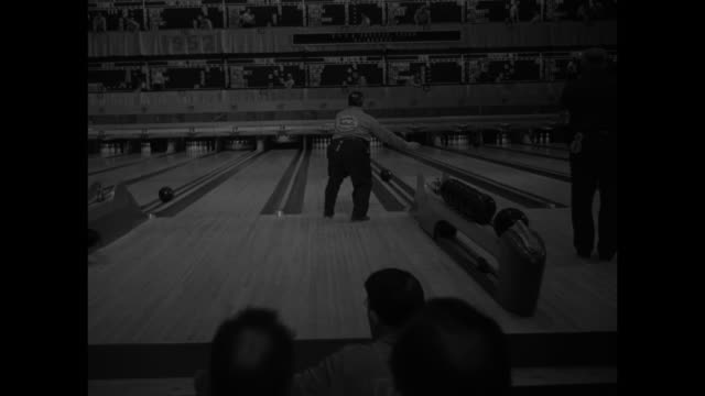 vídeos de stock, filmes e b-roll de cu bowling pins / high angle view of a long line of bowlers / man rolls ball down lane / pan of ball rolling to pins / another throws / scorekeepers... - setting clock