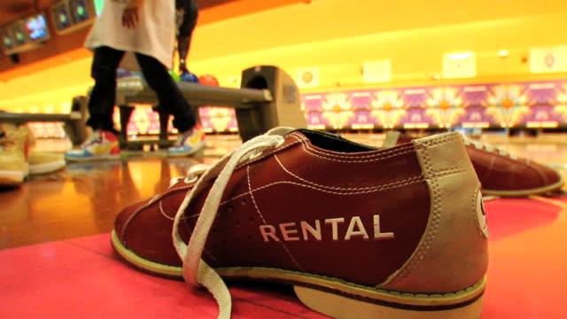 vídeos de stock, filmes e b-roll de bowling shoe w/ rental lettering sewn on side on floor in unidentifiable bowling alley, unidentifiable african american family in lanes bg. sports,... - sapato de boliche