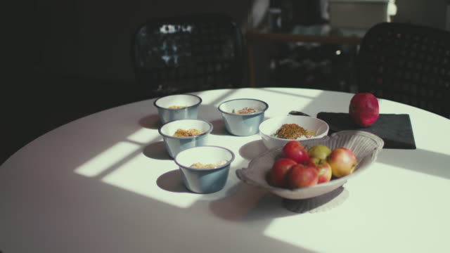 Bowls with healthy food, apples in sunlight on dining room table in residential home in Berlin, Germany