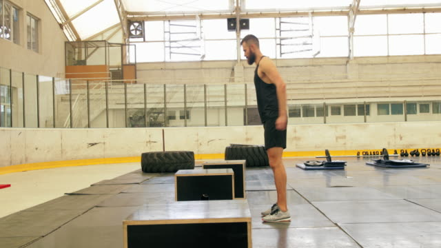 Box squat jumps in gym, panning shot
