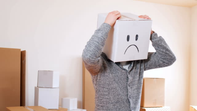 box with sad emoticon on head - one man only stock videos & royalty-free footage