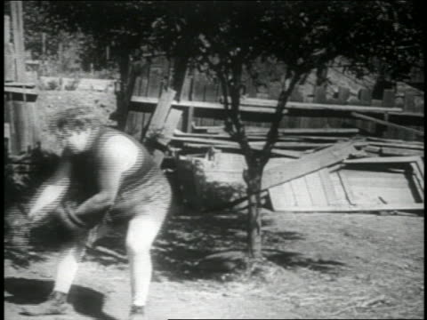 B/W 1914 boxer (Fatty Arbuckle) being pulled by rope falling on buttocks / feature
