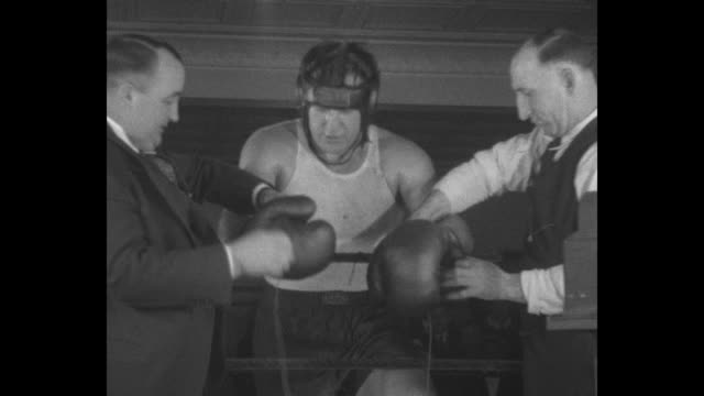 boxer jack sharkey in boxing gear and leaning on ropes of boxing ring talks with manager about upcoming fight with max schmeling / sharkey without... - primo carnera stock videos and b-roll footage