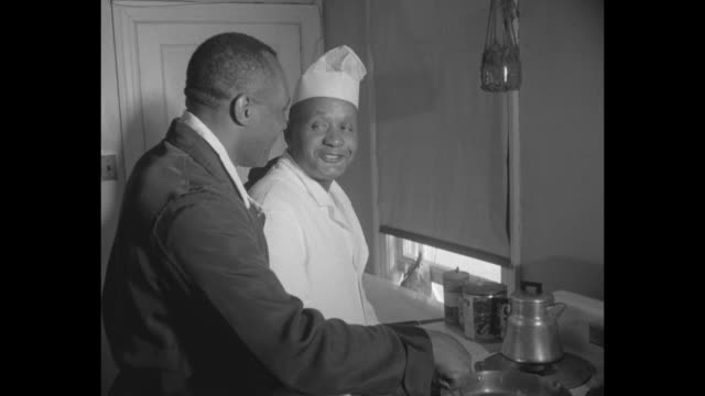 boxer jersey joe walcott at kitchen stove with man in chef's hat as he breaks eggs and stirs them in a stovetop pan / close shot as walcott stirs... - chef's hat stock videos and b-roll footage