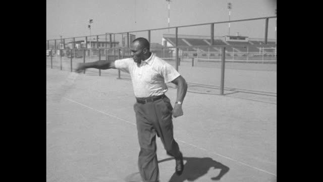 boxer jersey joe walcott runs with tennis racquet and misses hitting ball / walcott hits ball with racquet / walcott runs on court and hits ball with... - racquet stock videos & royalty-free footage