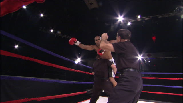 LA MS Boxer jumping around ring with his trainers, then one man lifts him up / Jacksonville, Florida, USA