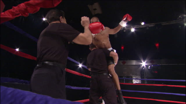 LA MS CU Boxer jumping around ring with his trainers, then one man lifts him up / Jacksonville, Florida, USA