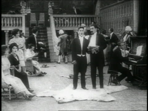 b/w 1914 boxer knocking man down stairs + running down stairs + disrupting fancy party / feature - 1914 stock-videos und b-roll-filmmaterial