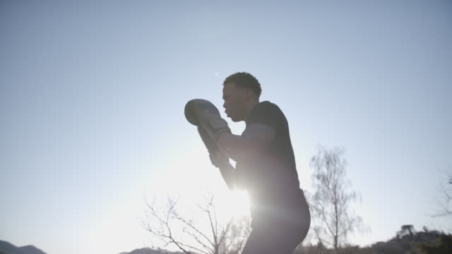 vídeos de stock, filmes e b-roll de boxeador ao ar livre soca em direção à câmera - sports training