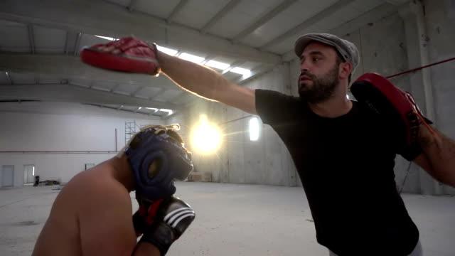 vídeos y material grabado en eventos de stock de sesión de trabajo de pad de boxeador con el entrenador en un antiguo edificio - calzoncillos bóxer