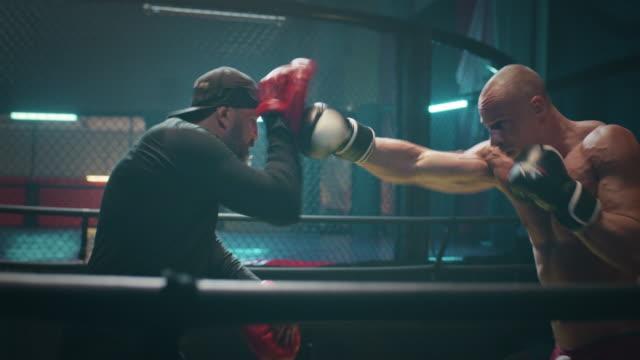 vidéos et rushes de séance de travail de pad de boxeur avec l'entraîneur. coups de pied rapides - agression