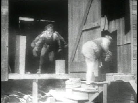 b/w 1914 boxer punching buttocks of 2nd boxer (fatty arbuckle) standing on stairs / gun firing - 1914年点の映像素材/bロール