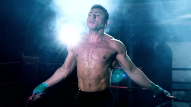 vídeos y material grabado en eventos de stock de boxer saltando cuerda en anillo de boxeo - cámara de aislamiento con guantes