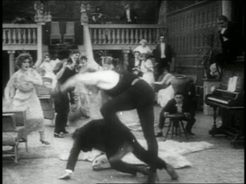 b/w 1914 boxer stumbling over man at party + running offscreen / feature - 1914 stock videos & royalty-free footage