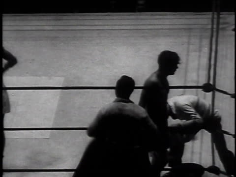 vídeos de stock, filmes e b-roll de boxer with arm around other boxer / men boxing / boxer knocked down - 1935