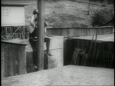 b/w 1914 boxer with gloves climbing from telephone pole onto roof of building / feature - building feature stock videos & royalty-free footage