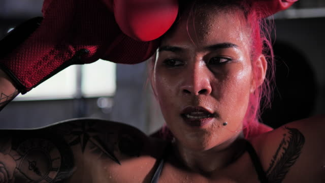 boxer woman sitting lifting the corner of the boxing ring, boxers asian women with tattoos of red hair. - punching stock videos & royalty-free footage