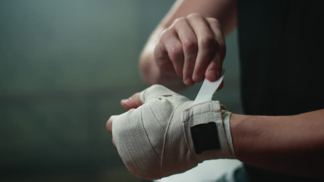 boxer wrapping bandages around his hand - glove video stock e b–roll