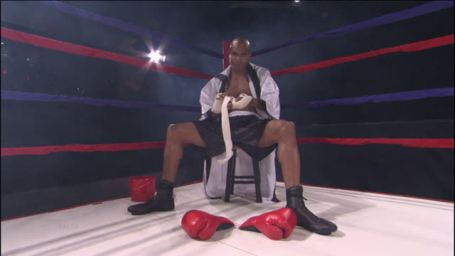 la ws boxer wrapping his hand with sports tape in corner of ring / jacksonville, florida, usa - 格闘技リング点の映像素材/bロール