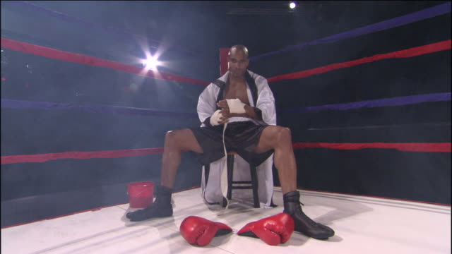 CU ZO LA WS Boxer wrapping his hand with sports tape in corner of ring / Jacksonville, Florida, USA